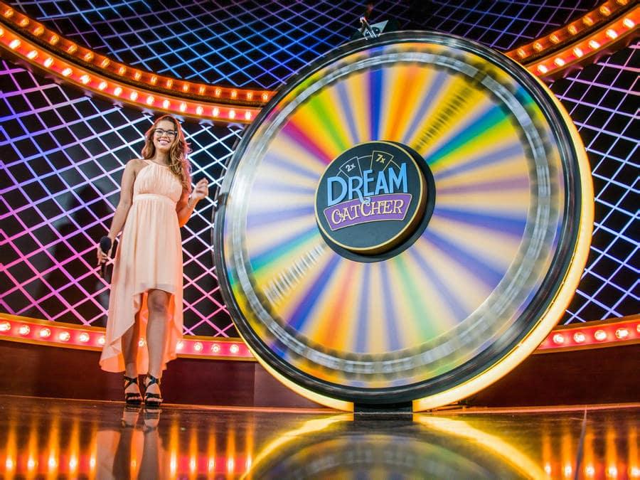Dream catcher onnenpyörä pyörii ja kaunis live casino diileri nainen seisoo pyörän vieressä
