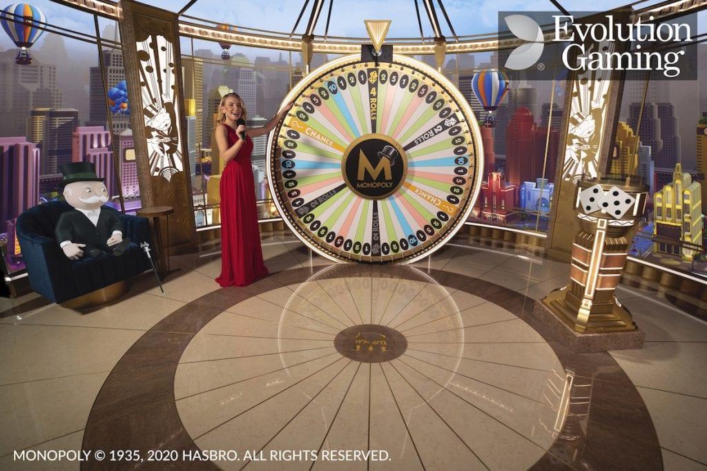 monopoly live onnenpyörä ja kaunis livecasino jakaja punaisessa mekossa pyörittämässä pyörää mr monopolyn sekä noppapelien kanssa